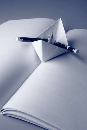 open trench: Concept with a paper boat, pencil and an open book