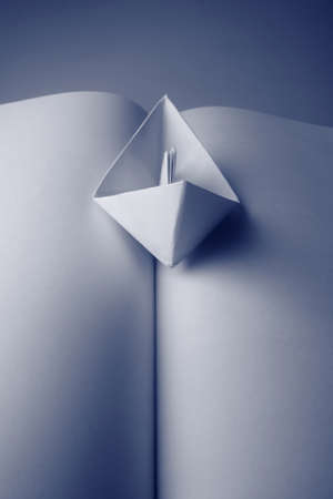 open trench: Concept with a paper boat and an open book