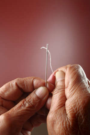 An senior woman trying to thread a needle Stock Photo