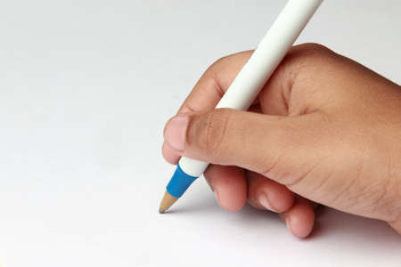 writing letter: Hand holding a pen writing on a white paper