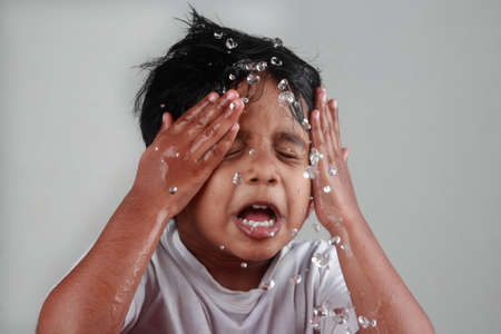 Pequeño muchacho que salpica el agua en su cara