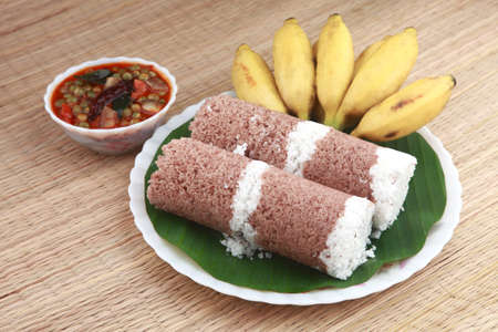 india food: Indian breakfast Puttu with curry and a bunch of banana. Stock Photo
