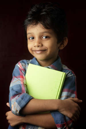 indian fair: Portrait of a little boy holding a book Stock Photo