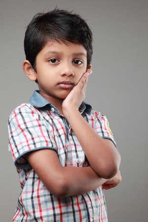 niño parado: Muchacho con una cara triste