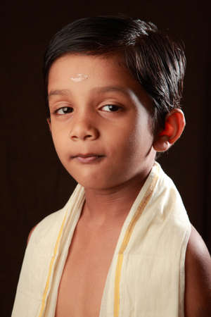 pious: Portrait of a traditionally dressed smiling Indian Hindu boy