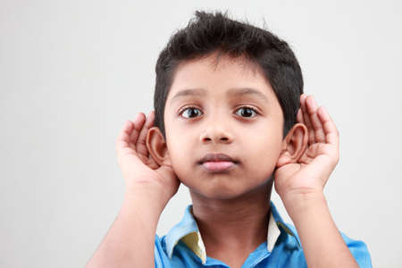keen: Boy keen on listening to a low voice Stock Photo