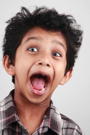 A boy screams with his mouth open Фото со стока