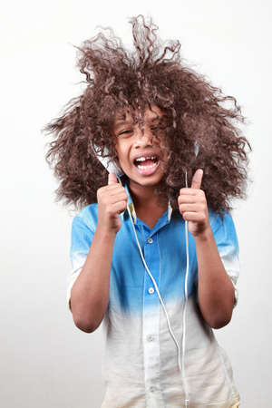 thumps up: A boy with a funky hairstyle in a playful mood Stock Photo