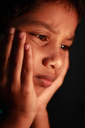sick boy: A boy looks in a depressed mood. Focus on eyes with shallow depth of filed