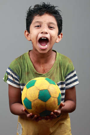 child education: Boy with body smeared with mud holds a football and shows energy