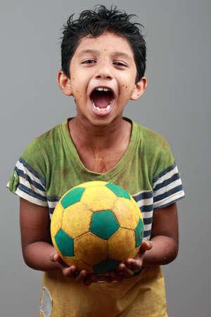 niño modelo: Muchacho con el cuerpo embadurnado de barro sostiene un balón de fútbol y muestra la energía