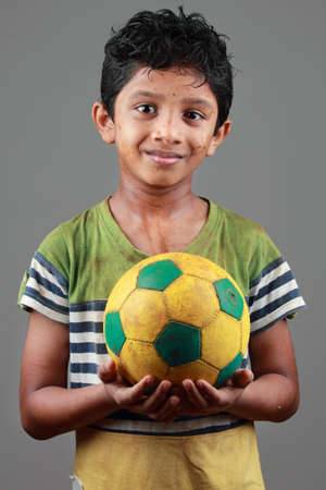 sports clothing: Boy with body smeared with mud holds a football Stock Photo