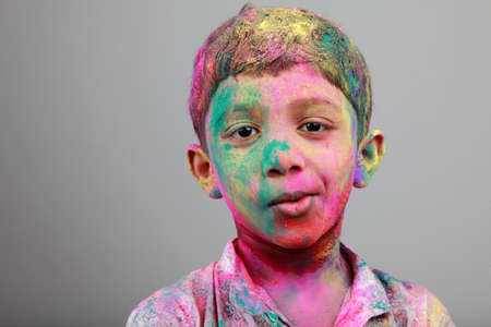vibrant colors: Smiling Portrait of boy with face smeared with colored powder. Concept for festival Holi