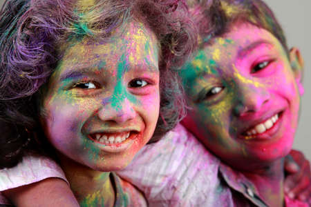 holi: Two Indian kids with face smeared with colors. Concept for Indian festival Holi.
