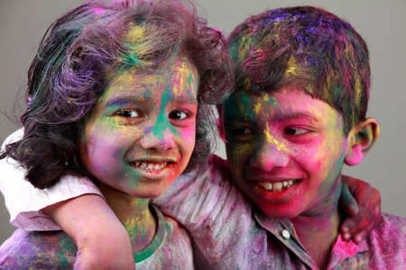 colored school: Two Indian kids with face smeared with colors. Concept for Indian festival Holi.