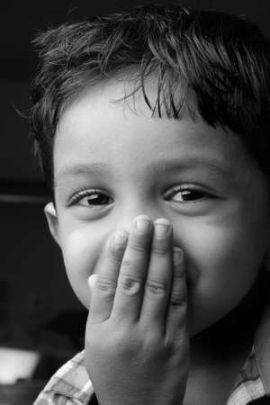 closed mouth: Black and white image of a boy smiles with closed mouth with hands