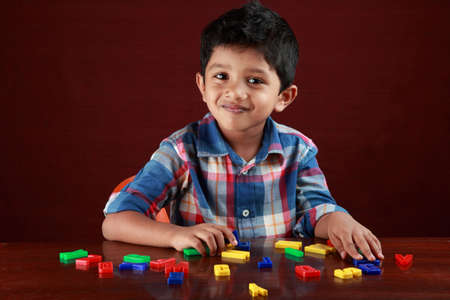 A small kid looks as he plays with toy alphabets in dark background