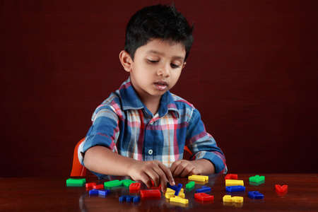 school activities: A small boy plays with toy alphabets in dark background