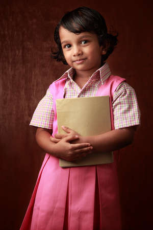 one little girl: Little girl in school uniform holds a book in hand Stock Photo
