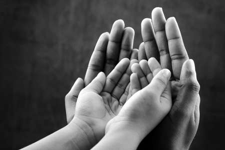 hold hands: Monochrome image of hands of a kid covered by hands of as elder. Ideal for concepts of care and protection