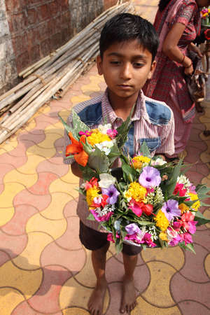 pune: PUNE, INDIA - APR 24, 2011-Unidentified vendors sell flowers in front of a temple in Pune, Maharashtra, India. Its custom ritual to offer flowers to deity in Hindu temples in India. Editorial