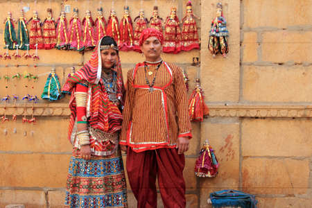 rajasthani: JAISALMER, INDIA - FEB 03, 2015-Unidentified Rajasthani couple dressed up in traditional costume and pose in front of a shop during Desert Festival in Jaisalmer, Rajasthan, India.