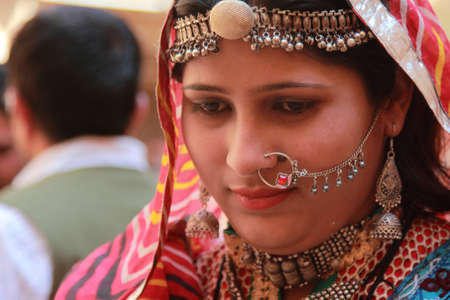 JAISALMER, INDIA - FEB 03, 2015- Unidentified Rajasthani woman dressed up in traditional costume and pose in front of a shop during Desert Festival in Jaisalmer, Rajasthan, India. Editorial