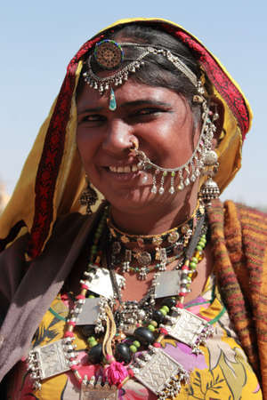 JAISALMER, INDIA - FEB 03,2015-Unidentified tribal woman dressed up in traditional Rajasthani costume and ornaments poses during Desert Festival  in Jaisalmer, Rajasthan, India.