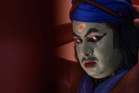 onstage: ULLANNOOR, INDIA - FEB 11,2015- An unidentified Kathakali artist does make-up before the on-stage performance during a temple festival in Ullannoor, Kerala,India.