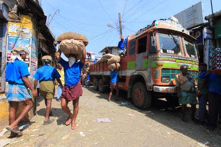 work force: KOCHI, INDIA -FEB 02,2012-Unidentified head load workers unloading gunny bags from a truck in the market  in Kochi, India. Head load workers are an organised work force in Kerala.
