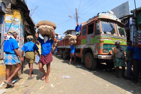 kochi: KOCHI, INDIA -FEB 02,2012-Unidentified head load workers unloading gunny bags from a truck in the market  in Kochi, India. Head load workers are an organised work force in Kerala.