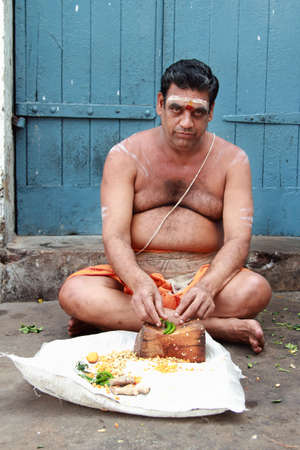appointed: CHENNAI, INDIA - FEB 09,2012- An unidentified Brahmin priest sits outside the Kapaleeshawar temple in Chennai, India. Brahmins are the appointed priests in most of the temples in India