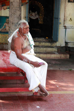 namaskar: CHENNAI, INDIA - FEB 09,2012- An unidentified Brahmin priest sits outside the Kapaleeshawar temple in Chennai, India. Brahmins are the appointed priests in most of the temples in India
