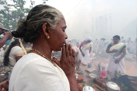 suffocating: ATTUKAL, INDIA - MAR 7,2012- An unidentified devotee prays during the Attukal Pongala in Attukal,Kerala,India.The event is considered as the largest gathering of women in the world.