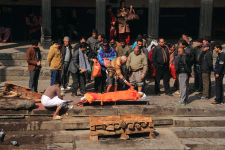 pyre: KATHMANDU - FEB 02,2014-Hindu people attend a religious cremation ceremony of a dead person at Pashupathinath cremation grounds at the banks of Bagmati river in Kathmandu, Nepal. Editorial