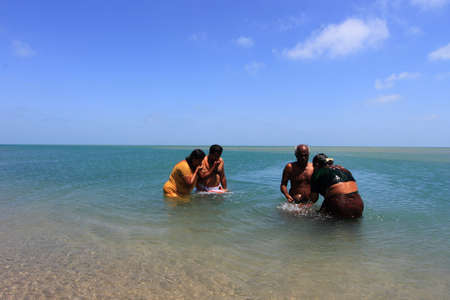 a bathing place: DHANUSHKODI, INDIA - OCT 06,2013- Unidentified Hindu family do rituals at the sacred confluence  in Dhanushkodi, Tamil Nadu, India. Dhanushkodi is a Hindu pilgrimage site in India. Editorial