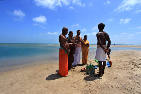 confluence: DHANUSHKODI, INDIA - OCT 06,2013- Unidentified Hindu family do rituals at the sacred confluence  in Dhanushkodi, Tamil Nadu, India. Dhanushkodi is a Hindu pilgrimage site in India. Editorial