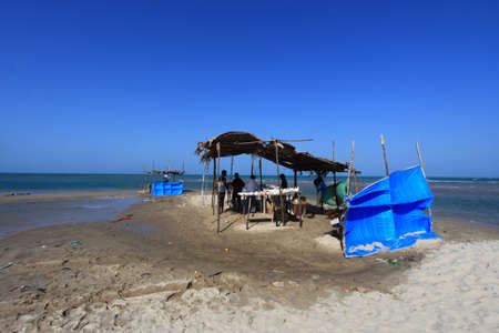 suffered: DHANUSHKODI, INDIA - OCT 05,2013- Locals operate temporary tea shops by the seaside in Dhanushkodi, Tamil Nadu, India. Dhanushkodi suffered major damage in a devastating cyclone in 1964