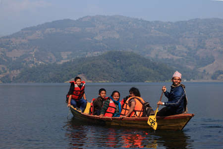 boating: POKHARA, NEPAL - FEB 06,2014-Unidentified tourists do boating in Fewa lake in Pokhara, Nepal. Pokhara is a popular tourist destination in Nepal known for trekking and boating.
