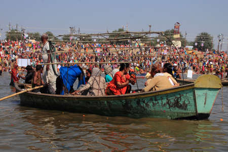 public offering: ALLAHABAD - FEB 08,2013-Devotees travel in boat to take bath in the river during the Kumbh Mela in Allahabad, India. Kumbh Mela is the largest religious human gathering in the world.