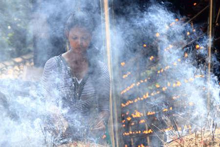 vihara: COLOMBO, SRI LANKA - DEC 11,2013-An unidentified Buddhist devotee burn incense sticks as a religious ritual at the Kelaniya Raja Maha Vihara in Colombo, Sri Lanka.