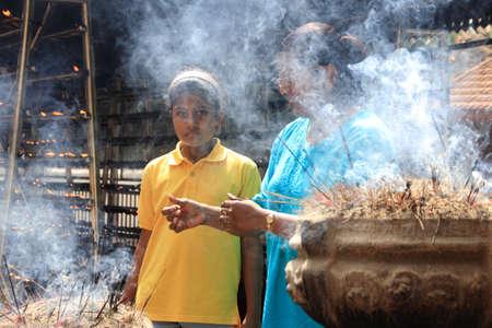 devotee: COLOMBO, SRI LANKA - DEC 11,2013-An unidentified Buddhist devotee burn incense sticks as a religious ritual at the Kelaniya Raja Maha Vihara in Colombo, Sri Lanka.