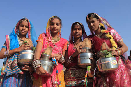 rajasthani: JAISALMER, INDIA - FEB 01,2015-Traditionally dressed Rajasthani dancers holding pots perform during a cultural procession for Desert festival held in Jaisalmer, Rajasthan,India. Editorial
