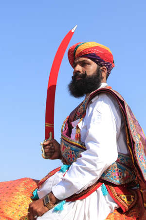 rajasthani: JAISALMER, INDIA - FEB 01,2015-Traditionally dressed Rajasthani man holding sword rides on a camel during a cultural procession for Desert festival held in Jaisalmer, Rajasthan, India.