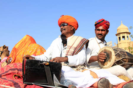 rajasthani: JAISALMER, INDIA - FEB 01,2015-Traditionally dressed Rajasthani folk singers perform during a cultural procession for Desert festival held  in Jaisalmer, Rajasthan, India.
