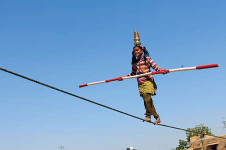 uneducated: JAISALMER, INDIA - FEB 03, 2015- An unidentified Indian girl performs street acrobatics by walking the rope during the Desert Festival in Jaisalmer, Rajasthan, India.
