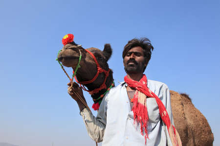villager: PUSHKAR, INDIA - NOV 19,2010- An unidentified villager with his camel participate in Pushkar Fair in Pushkar, India. Camels are the top selling livestock in the Pushkar Fair.