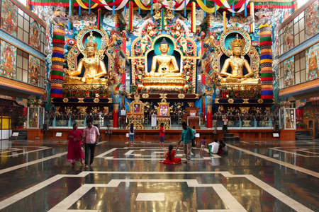local 27: BYLAKUPPE, INDIA - MAR 27, 2015- Local tourists visit the Namdroling Monastery after prayer  in Bylakuppe, India. Bylakuppe second largest Tibetan refugee settlements in India.