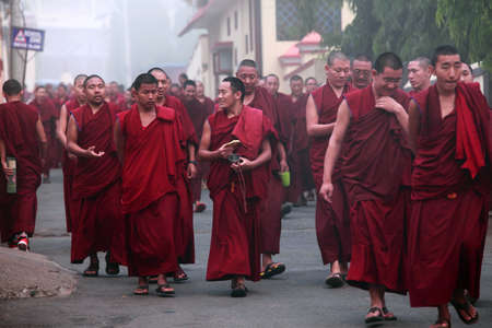 settlements: BYLAKUPPE, INDIA - MAR 29, 2015-Unidentified Buddhist monks walk in group for morning prayer in Bylakuppe, India. Bylakuppe is second largest Tibetan refugee settlements in India. Editorial