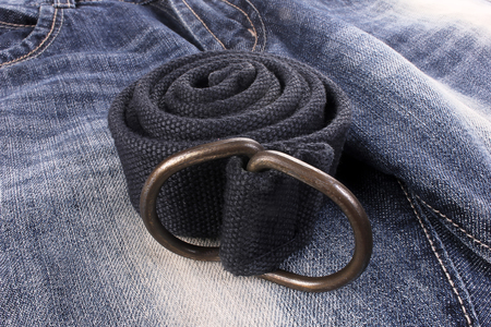 a rolled-up belt on old blue jeans